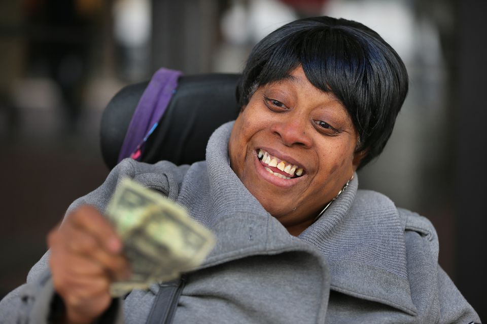 """Rhonda Gibson, from Malden, examined the bills she received at Downtown Crossing. Gibson, who is in a wheel chair, said """"Now I have my bus money to get home."""""""