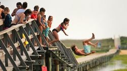 Youngsters jump from the beloved Sandwich boardwalk into the water of the marsh below. A landmark since the 19th century, the boardwalk is now slated to be replaced. Preservationists are fighting to save it.