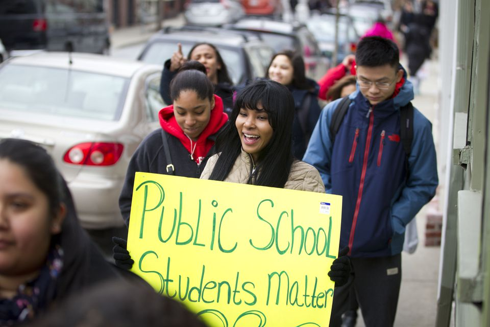 Lorena Paulino (center with sign), a senior at Charlestown High School, was among the dozens of Charlestown High School students who participated in the walkout.