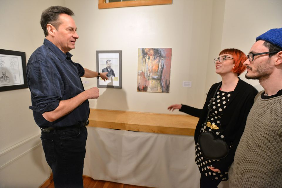 Artist Gary McManus, a guard at the Museum of Fine Arts, shows his portrait of late artist and colleague Zlatko Fedotov to Fedotov's daughter, Nina, and her partner, Michael Richards, at Gallery 263 in Cambridge.