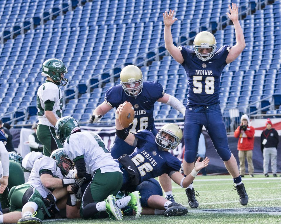 Hanover senior back Brad Rogers (22) raises the ball and his arm, signaling a touchdown against Grafton at Gillette Stadium.