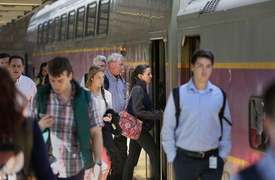 Passengers board a Keolis-run MBTA commuter train to Framingham at South Station.