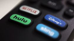 The logos for Netflix, Hulu, Disney Plus, and Sling TV are pictured on a remote control.