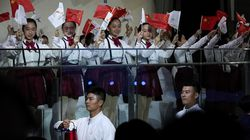 Children wave Chinese national flags and Beijing 2022 Winter Olympic Games flags as volunteers carrying the Olympic torch and the frame arrive to a welcome ceremony for the Frame of Olympic Winter Games Beijing 2022, held at the Olympic Tower in Beijing, Wednesday, Oct. 20, 2021.