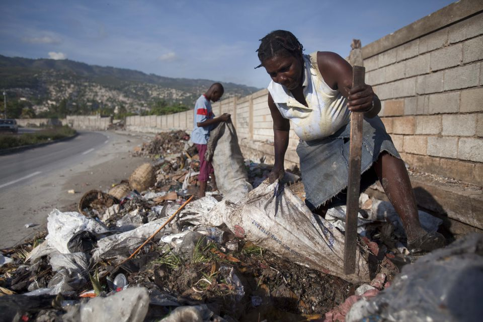Marie Satty, 52, dug  through roadside trash in Carrefour, Haiti, for empty plastic bottles to sell to a recycling center.