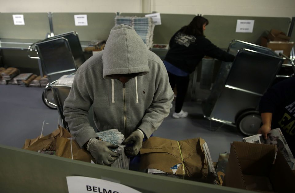 A Globe delivery worker bundled papers and bagged them in a distribution center in Woburn earlier this month.