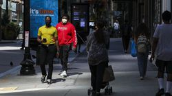 Crowds of people walked through downtown Boston on Wednesday, some wearing masks and some not. The Centers for Disease Control and Prevention changed course Tuesday on some masking guidelines, resulting in people donning masks both indoors and out.
