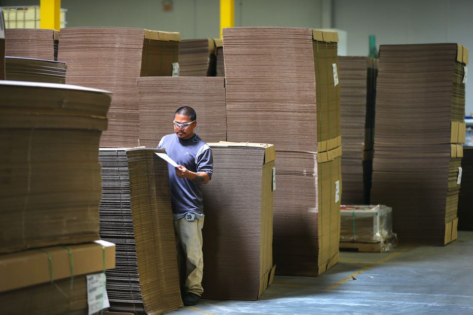 Abbott-Action has a state of the art corrugated box-making facility. A worker checked the label on one of the stacks of precut boxes that were ready to be shipped out. The boxes lie flat in the stacks and are folded into shape by the clients.