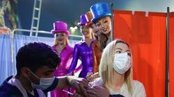 Rhiannon Alexander, 34, from Bradford receives a Covid 19 vaccination as circus performers look on during a staged photo at a new 'Pop Up' vaccination centre in the Big Top of Circus Extreme in Shibden Park on July 31.