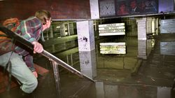 Benjamin Stell, an MBTA consultant, stands on the steps of the Kenmore Square MBTA station on Oct. 22, 1996. The station was submerged with more than 6 feet of water, though it had actually dropped from its peak level which was up to the clock on the ceiling.