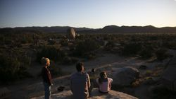 In this May 19, 2020, file photo, Aaron Stubbs and his two children watch the sunset at Joshua Tree National Park in California. The Biden administration is outlining a plan to sharply increase conservation of public lands and waters over the next decade.