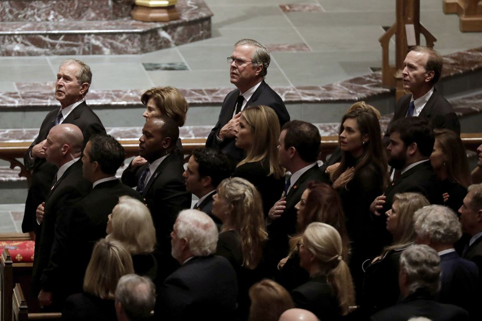 Former President George W. Bush (left) and his brothers former Florida Gov. Jeb Bush and Neil Bush sang during a funeral for former President George H.W. Bush.