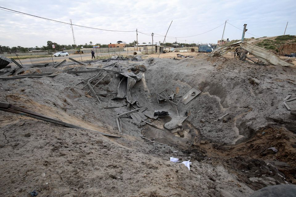 A Palestinian man walked past a crater on the ground following an Israeli air strike targeting a site belonging to Gaza's Islamist rulers Hamas, in Khan Yunis in the southern Gaza Strip March 15, 2019.