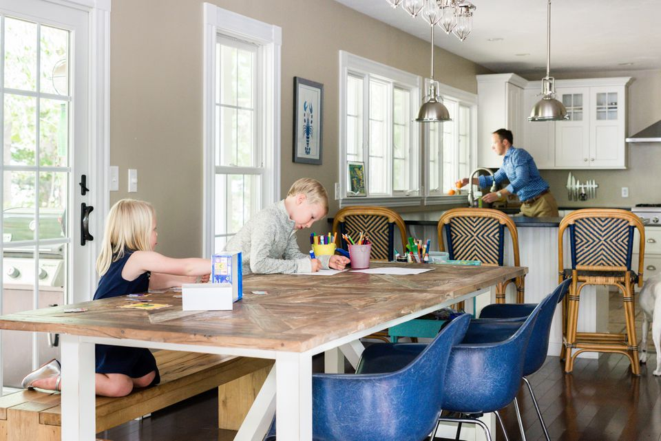 "Tess and Emmett color while Will preps a meal. The Restoration Hardware kitchen table has a rustic wood top, and the blue chairs are from Design Within Reach.  A large part of the home's appeal was its open floor plan. ""I love how I can be cooking in the kitchen and the kids are right nearby,"" says Lindsey."
