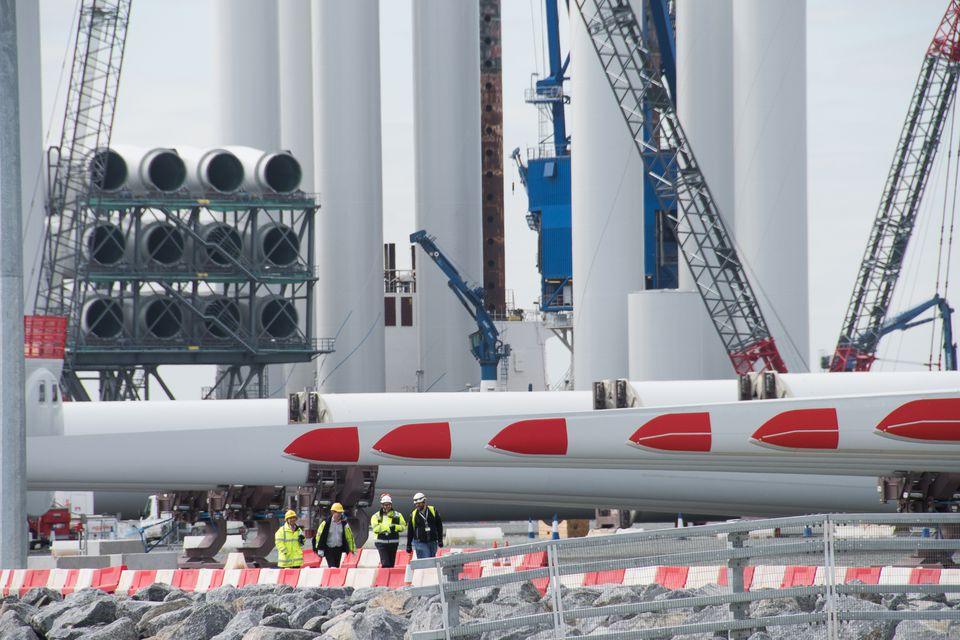 Siemens workers dwarfed by offshore wind blades and towers being deployed from Hull, England.  More than 6,000 jobs are projected to come to the Hull and Grimsby area, making it the center of the United Kingdom's offshore wind industry.
