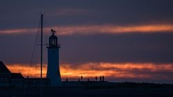 People line up next to the Old Scituate Lighthouse to watch an eclipsed sunrise on June 10, 2021. in Scituate.
