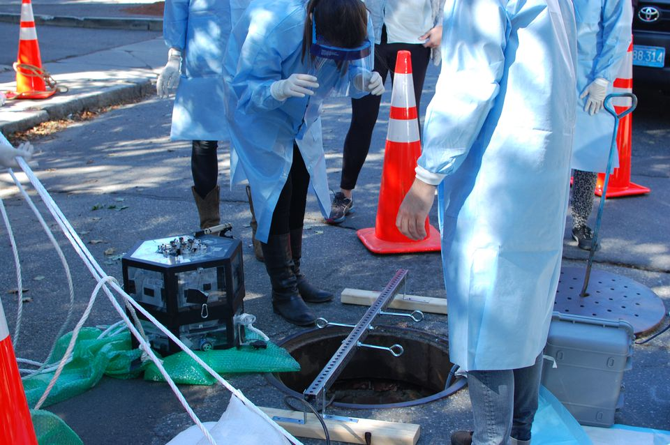 MIT's Ghaeli peers into a Cambridge manhole in 2015; at her feet is Mario, the prototype sewer-bot.