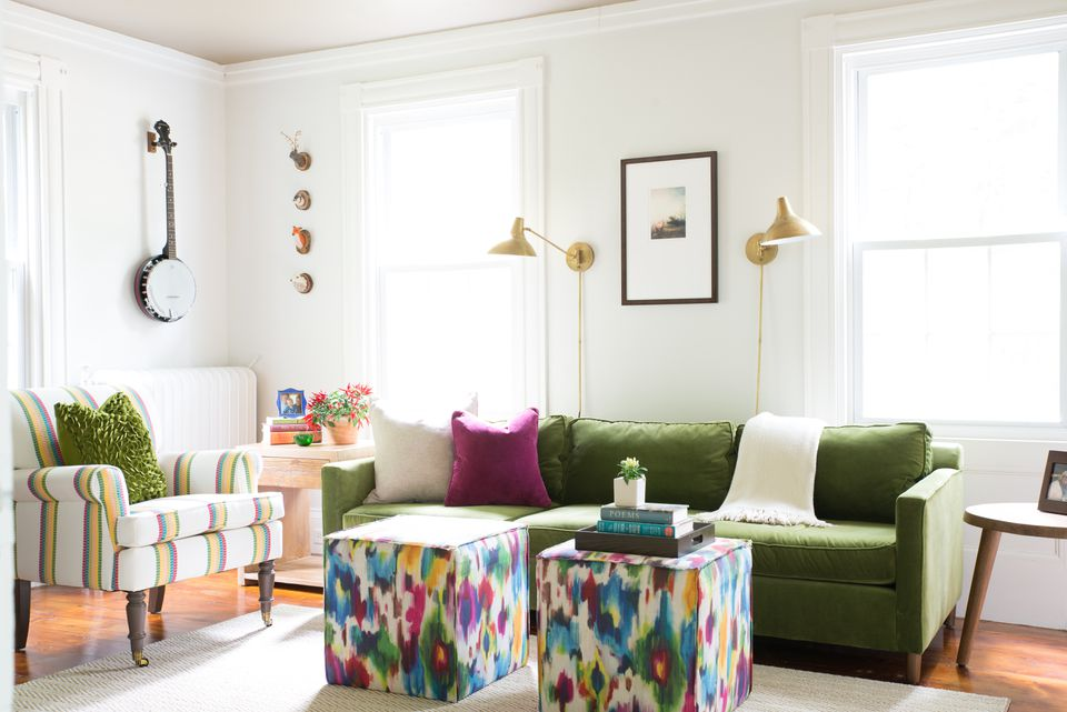 In the den, the striking green  velvet sofa complements a  custom chair upholstered in Lee Jofa striped fabric and grounds colorful ottomans from Wayfair.