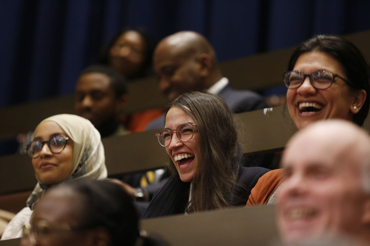 Fellow congresswomen-elect Alexandria Ocasio-Cortez (C) and Rashida Tlaib (R) laughed as other City Councilors referenced them in their farewell speech to Ayanna Pressley at City Hall.