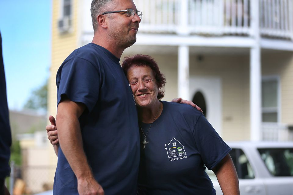 Charlene Cruz hugs David Vanderbilt, co-owner of Coastal Windows & Exteriors, which helped put on a new roof and deck and install new  windows on her Peabody home.
