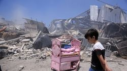 A Palestinian boy near the ruins of his house after an Israeli airstrike in Gaza City, Gaza Strip, on Friday. Civilian deaths on both sides raise urgent questions about which military actions are legal, what war crimes are being committed, and who, if anyone, will be held to account.