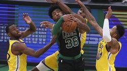 Marcus Smart pulls down an offensive rebound in between Warriors forward Andrew Wiggins (left), center Kevon Looney and forward Kent Bazemore (right) late in the fourth quarter of the Celtics' 119-114 victory against Golden State Saturday.