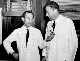 Dr. Paul Zoll (at left) holds an electrical apparatus successfully used in heart patients.