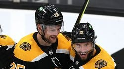 Bruins defenseman Brandon Carlo (left) celebrates his third-period goal teammate Craig Smith (right) in Thursday night's victory over the Rangers.
