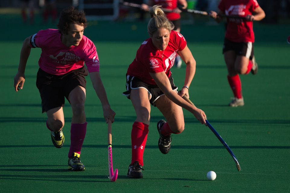 Katie Kelly, a player in the the North East Field Hockey League, dribbles through traffic during a game at Harvard's Jordan Field in Allston.