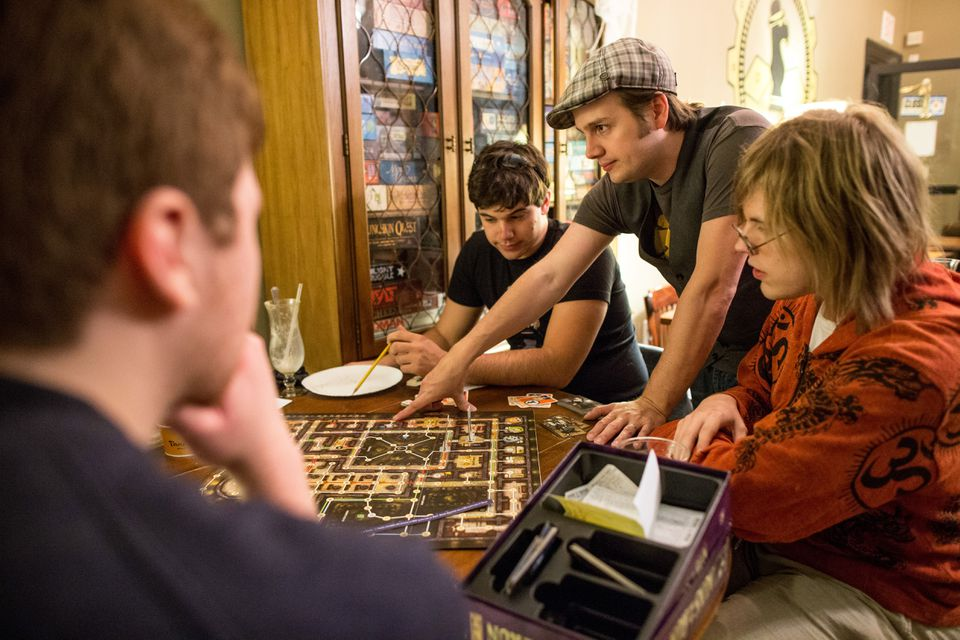 At Brookline's Knight Moves cafe, owner Devon Trevelyan (center) offers some tips for playing Nuns on the Run.