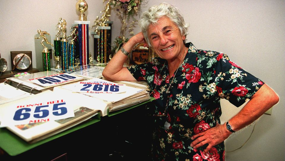 Mrs. Rossetti, who kept scrapbooks with the results of every race she ran, posed with a few of her bibs and trophies in 1998.