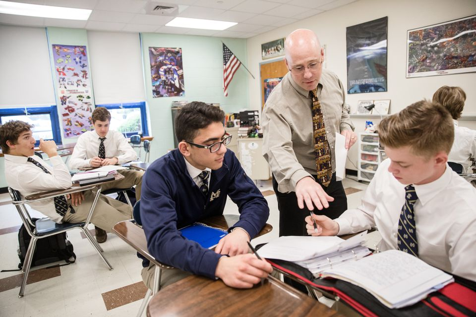 Eamonn Casey, center, helped students Dominic Odoguardi, left, and Kirill Mastracola, right, during a theology class at Malden Catholic High School.