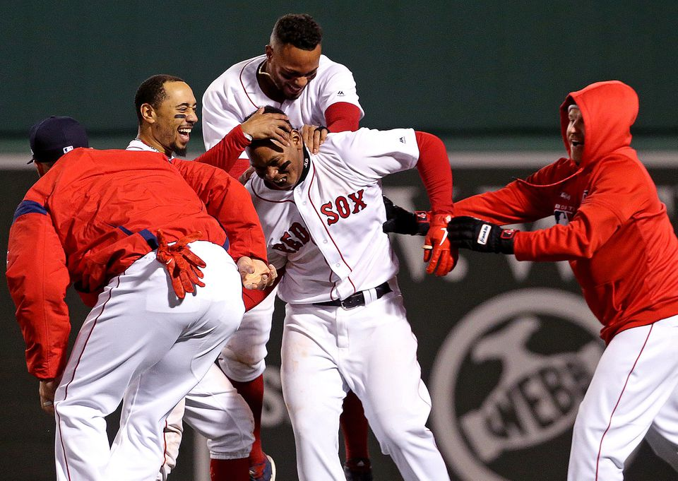 Rafael Devers is mobbed by teammates after his game-winning single in the ninth inning.