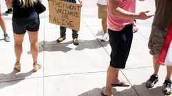Anti-vaccine rally protesters hold signs outside of Houston Methodist Hospital in Houston, Texas, on June 26.