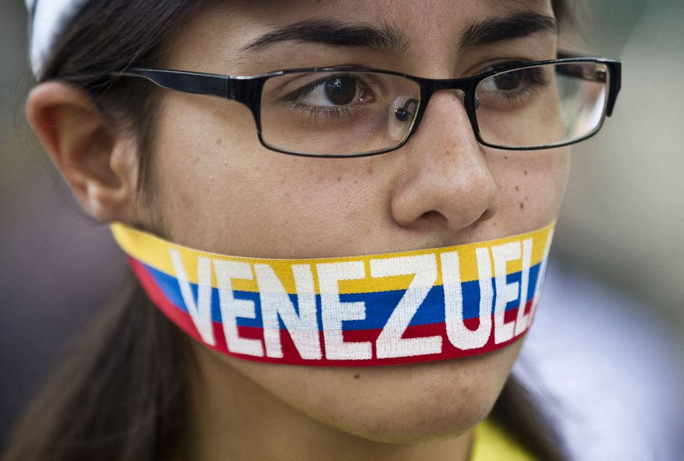 An antigovernment demonstrator stood with a ribbon covering her mouth during a protest in front of an office of the Organization of American States in Caracas.