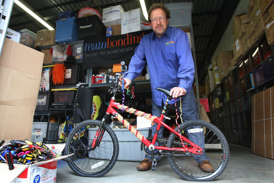 David Goldstein at TeamBonding's Stoughton facility with the focus of one project — assembling bikes for charity.