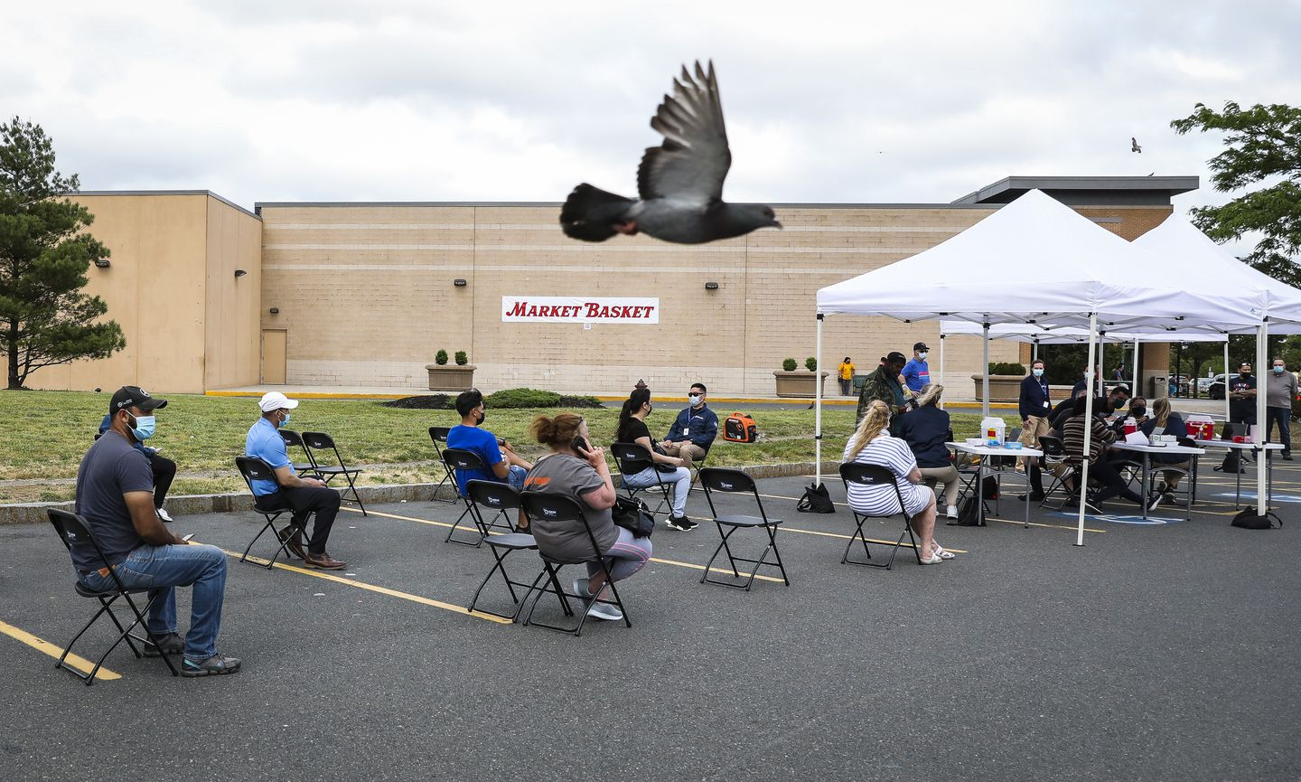 People waited for 15 minutes after receiving their COVID-19 vaccine at mobile clinic outside of Market Basket in Chelsea on Thursday.