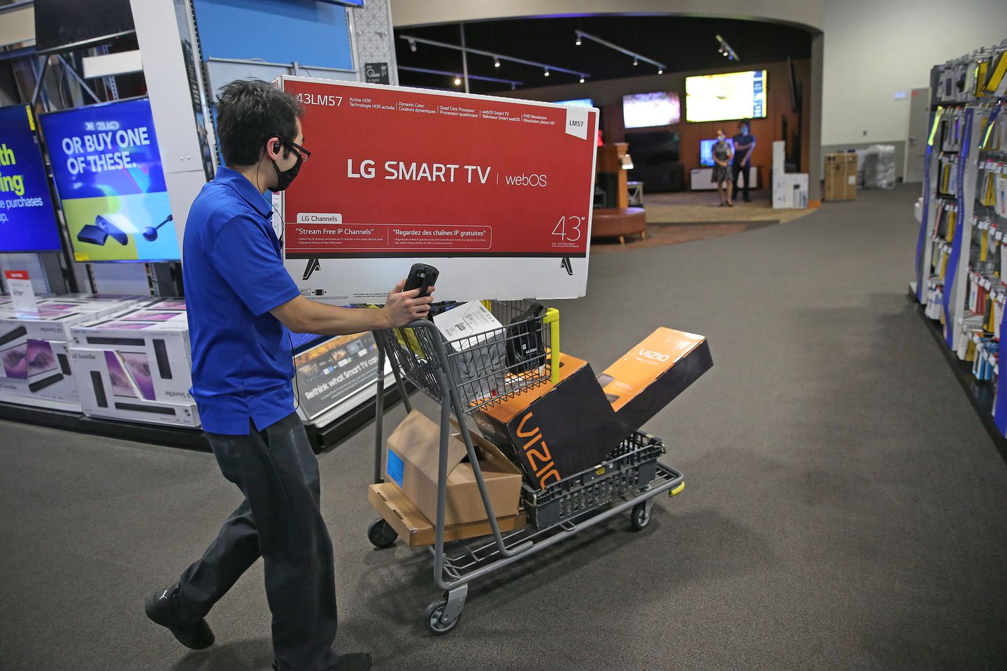 A Best Buy employee uses a cart to do shopping for an online customer.