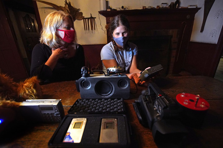 "Reporter Amanda Milkovits, left, and her sister Susanne Carpenter listen to a ""Spirit Box."""