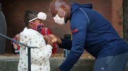 Dauda Sesay helps his daughter, Sudiatu, 6, with her jacket while dropping her off for her first day of 1st grade at the Lincoln-Hancock Community School in Quincy on Sept. 17, 2020.