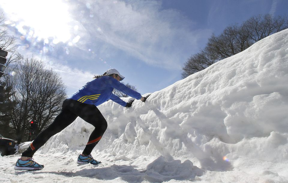 Becca Pizzi used a snowbank to stretch as she trained along Heartbreak Hill on Feb. 27.