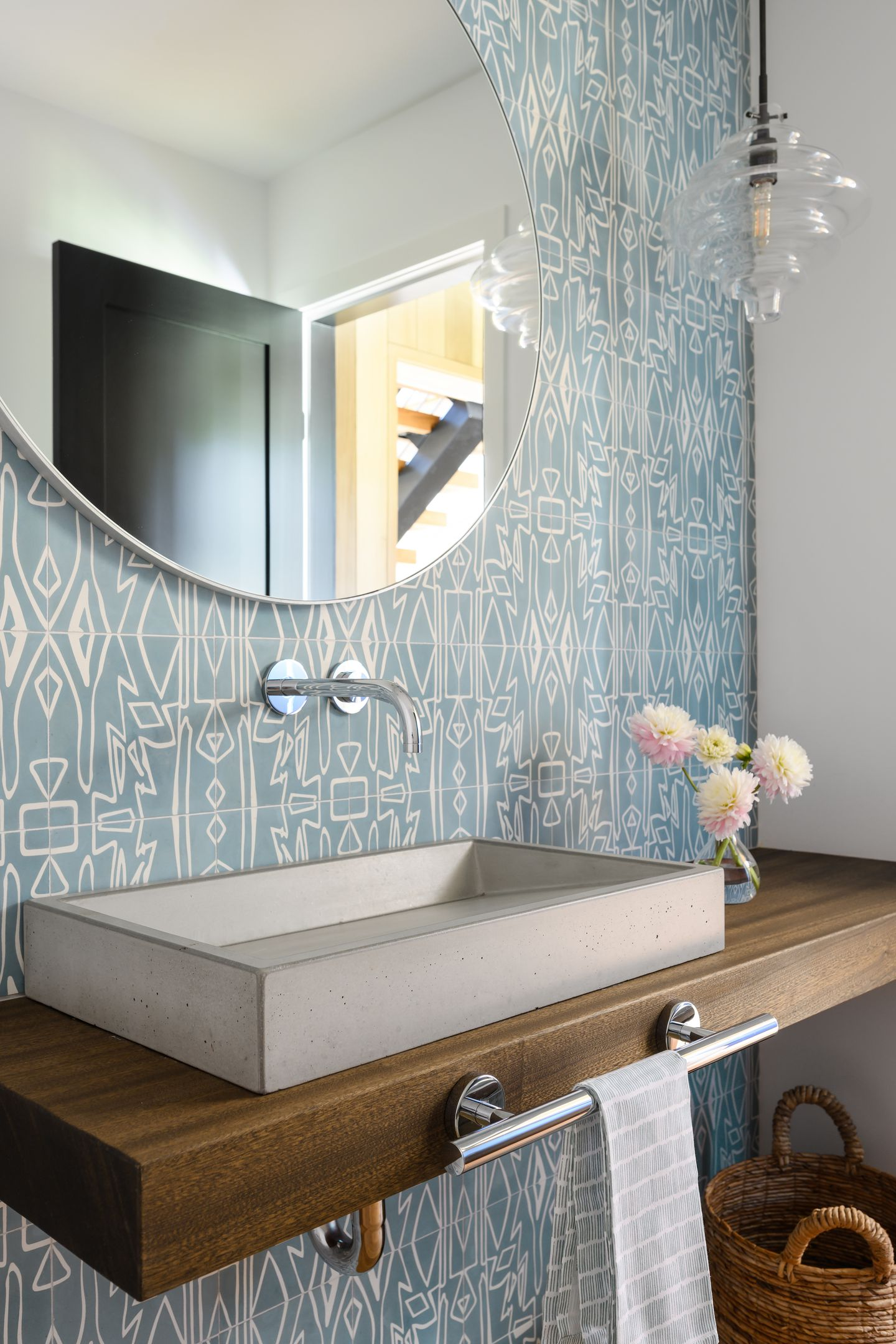Cement tiles by Eskayel for Cle bring color to a powder room; the pendants by Kelly Wearstler for Visual Comfort are from Newburyport Lighting; and the concrete sink ties to the lower level floor.