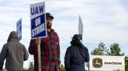 Deere & Co. workers hold signs during a strike outside the John Deere Des Moines Works facility in Ankeny, Iowa on Oct. 15.