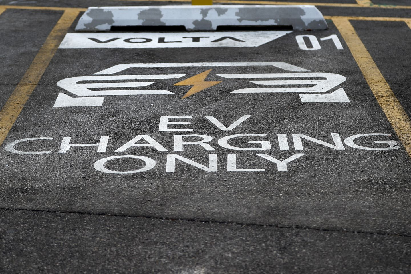 A designated parking space for electric vehicles at a Chicago area grocery store. Massachusetts will need to build a dense network of charging stations for residents to adopt electric vehicles.