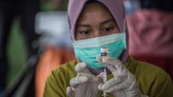 A health worker prepares a syringe of the Sinovac Covid-19 coronavirus vaccine at a makeshift mass vaccination centre on a football field in Surabaya on July 29, 2021.