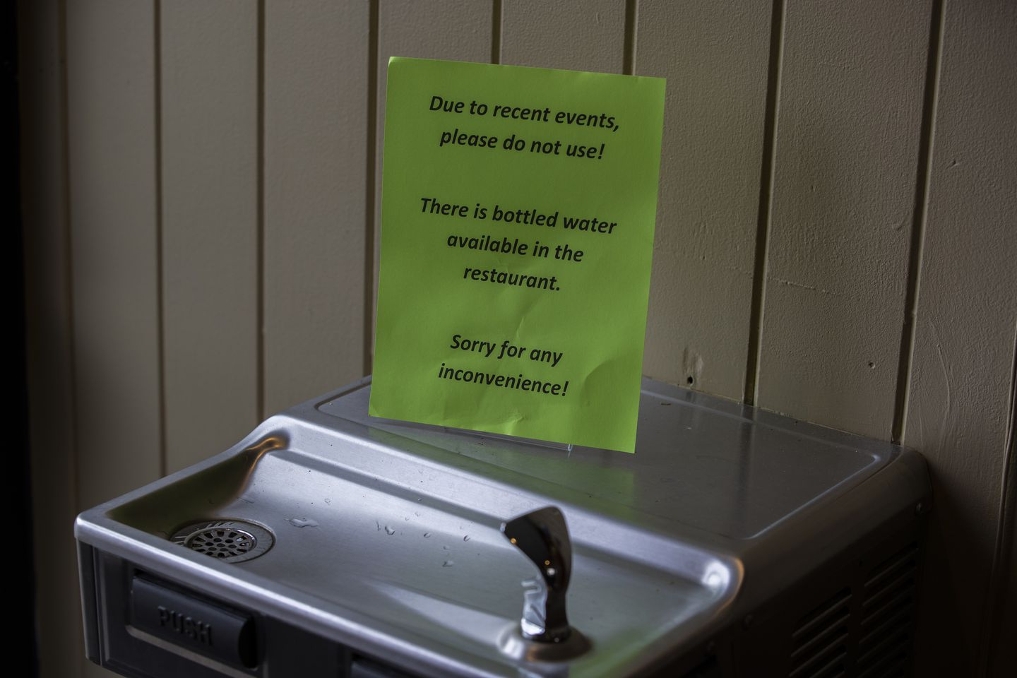 A sign warned patrons to avoid using a shared water fountain.