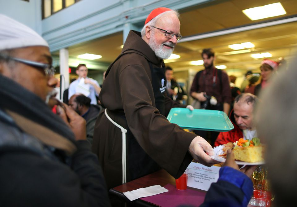 Cardinal Sean P. O'Malley said a prayer and then served a plate at the Christmas Eve luncheon.