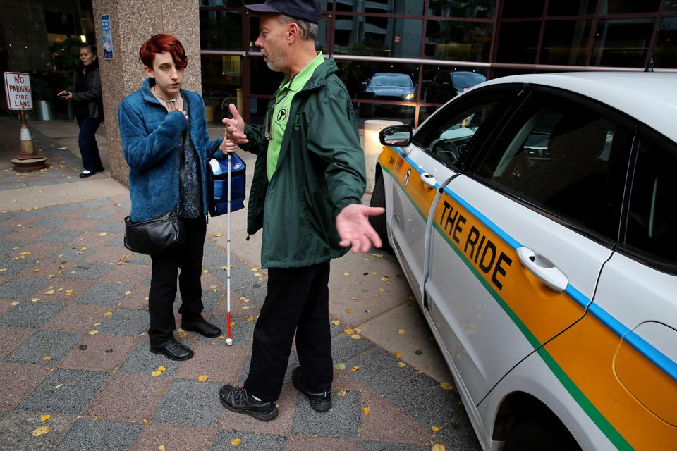 Passenger Mandi Curtis, of Roxbury, talked with The Ride driver Manny Rebello outside Boston Medical Center.