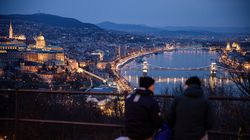Visitors look out over the city skyline and the Chain Bridge at night in Budapest.