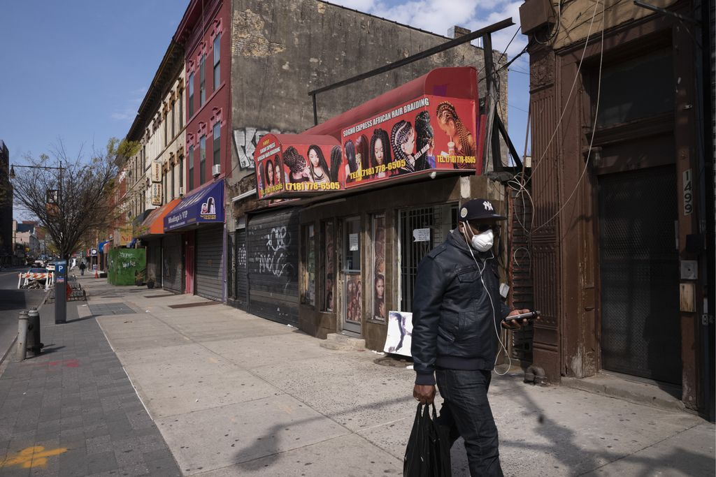 A man wearing a mask walked past Brooklyn's Sogho Express African Hair Braiding salon, which is closed due to the coronavirus pandemic.MARK LENNIHAN/ASSOCIATED PRESS